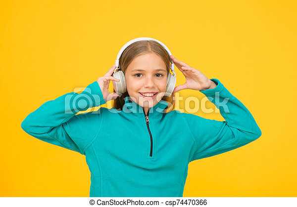 Face the music. Little child listen to music yellow background. Small child enjoy music playing in earphones. Like music to my ears - csp74470366