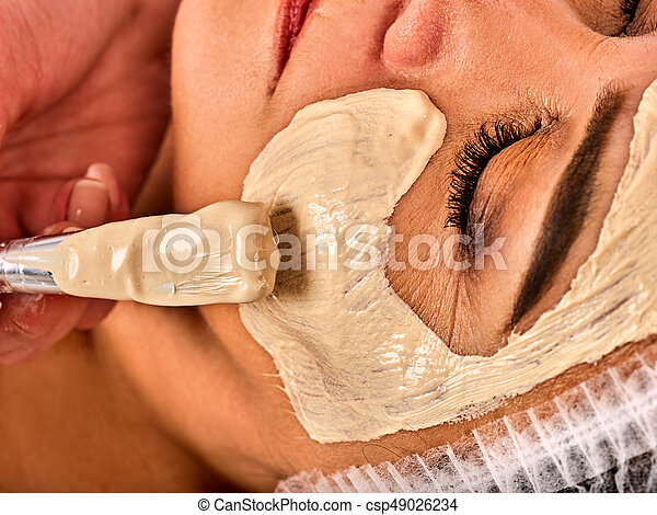 Facial mask and massage for forty five year old woman. Cropped shot of woman middle-aged take face cleaning by therapeutic mud in spa salon. Recipe for preserving youth.