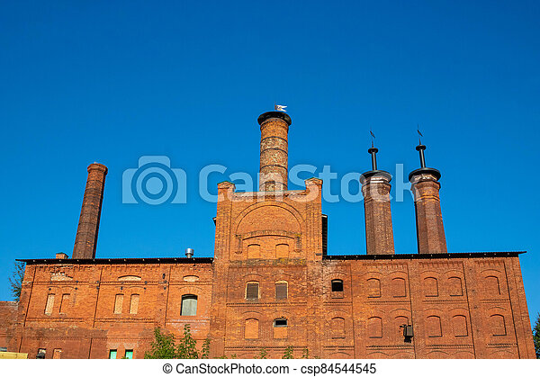 Factory brick chimneys on a red old building against a blue sky - csp84544545