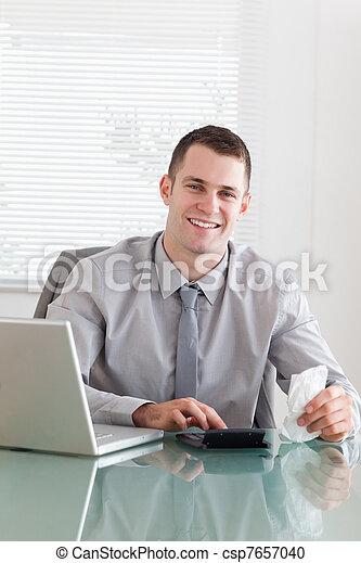 Un hombre de negocios feliz comprobando una factura - csp7657040