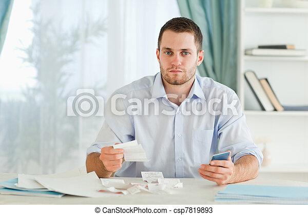 Hombre de negocios con calculadora comprobando facturas - csp7819893