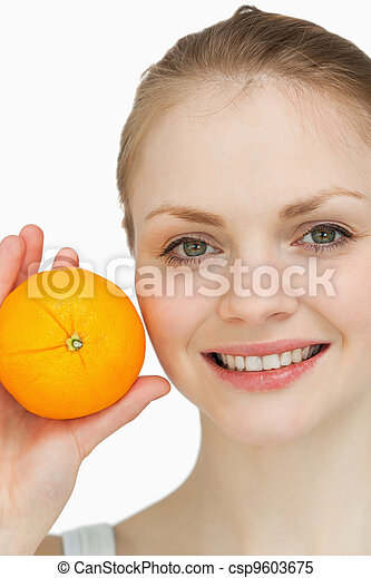 Fair-haired woman presenting an orange - csp9603675