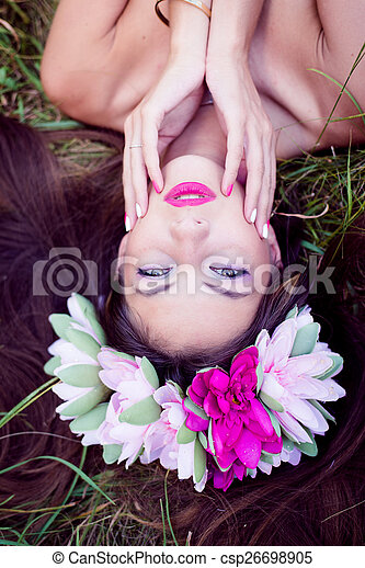 fairy girl: closeup on beautiful young lady having fun lying relaxing on green grass outdoors copy space background - csp26698905