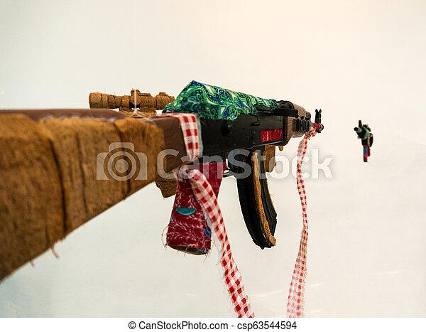 Fake AK Kalashnikov assault rifle hanging on white background - csp63544594