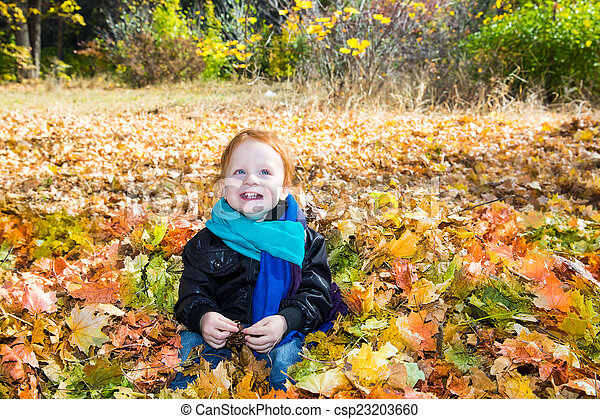 Fall. Adorable child boy with leaves in autumn park - csp23203660