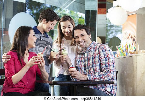 Un hombre feliz comiendo helado con su familia - csp36841349