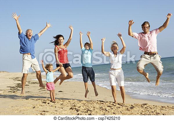 Retrato de tres generaciones de familia en vacaciones en la playa saltando en el aire - csp7425210