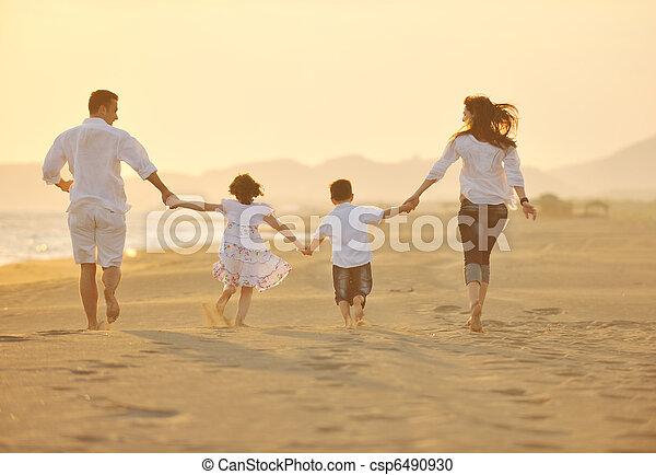 Una familia feliz se divierte en la playa al atardecer - csp6490930