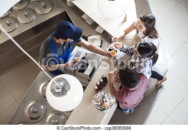 Familia eligiendo tazas en el mostrador en la heladería - csp38083666