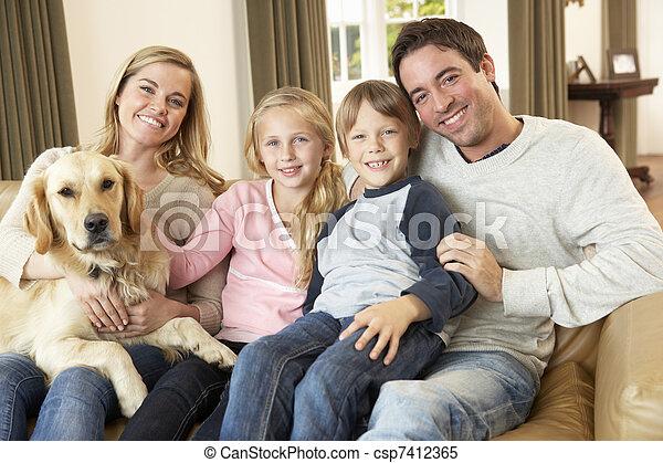 Una familia feliz sentada en el sofá sosteniendo un perro - csp7412365