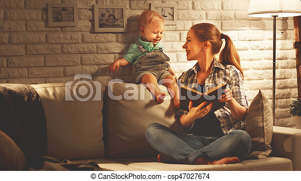 Family before going to bed mother reads to her baby son book near a lamp in the evening - csp47027674