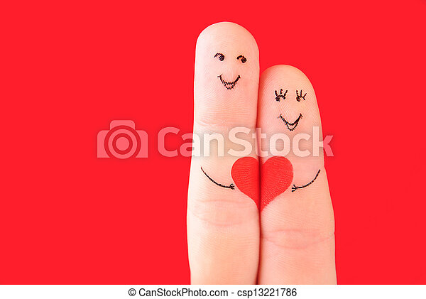 family concept - a man and a woman hold on the red heart, painted at fingers and isolated on red background - csp13221786