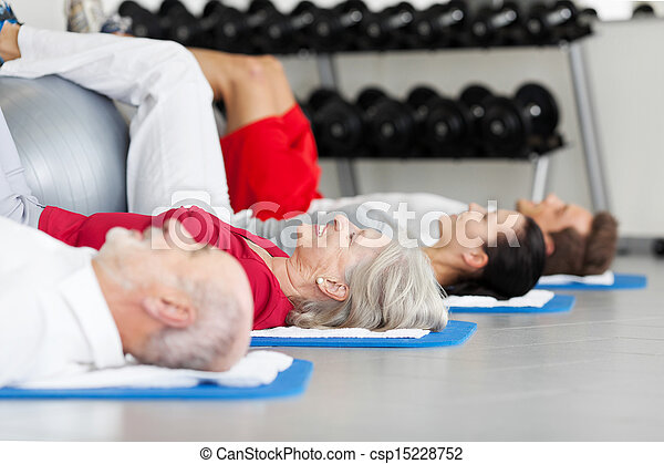Family Exercising While Lying On Mat At Gym - csp15228752