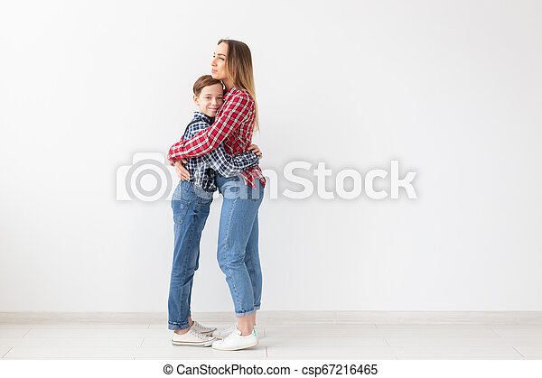 Family, fashion and mothers day concept - Portrait of mother and son dressed in plaid shirts on white background with copy space - csp67216465