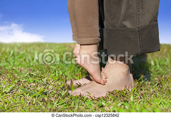 Family feet on the grass with cloud background - csp12325842