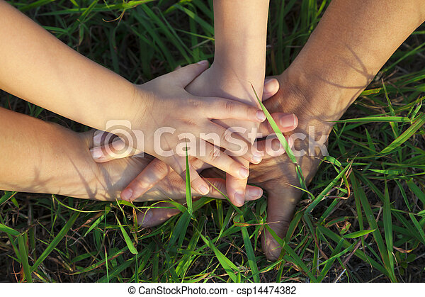family hand stack together on the grass - csp14474382