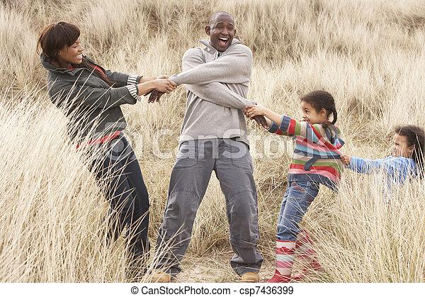 Family Having Fun In Sand Dunes - csp7436399