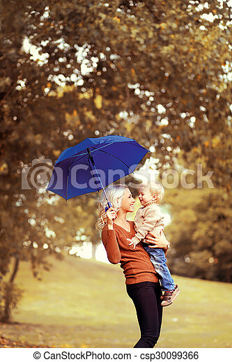 Family in autumn! Happy mother and child with umbrella having fun together - csp30099366