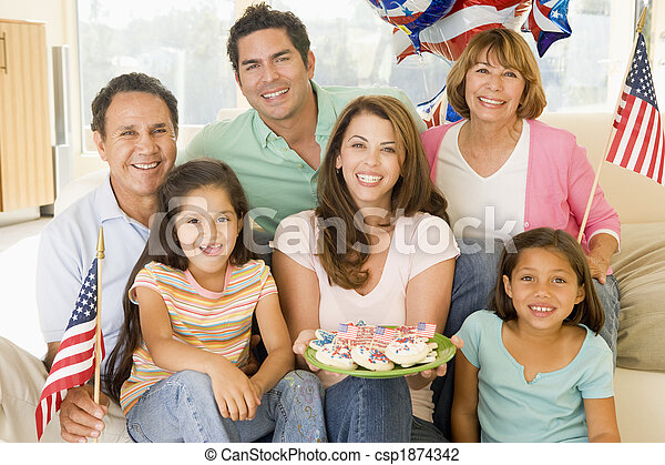 Family in living room on fourth of July with flags and cookies s - csp1874342