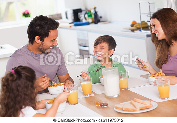 Family laughing around breakfast - csp11975012