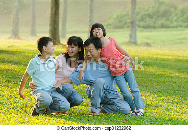 Family lying outdoors being playful and smiling, Outddor portrait - csp31232962