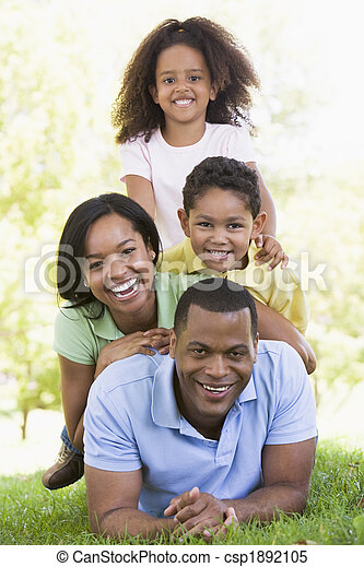 Family lying outdoors smiling - csp1892105