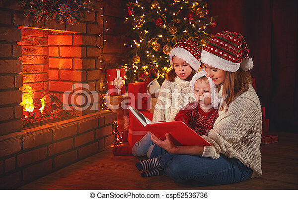 Mother Christmas.Family Mother And Children Read A Book At Christmas Near Fireplace At Home