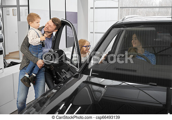 Family observing new automobile in car dealership. - csp66493139