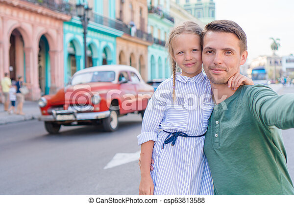 Family of dad and little girl taking selfie in popular area in Old Havana, Cuba. Little kid and young father outdoors on a street of Havana - csp63813588