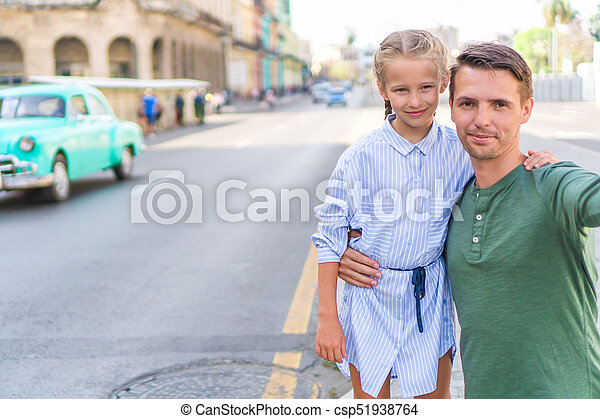 Family of dad and little girl taking selfie in popular area in Old Havana, Cuba. Little kid and young father outdoors on a street of Havana - csp51938764