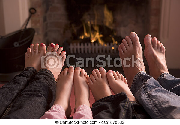 Family of feet warming at a fireplace - csp1878533