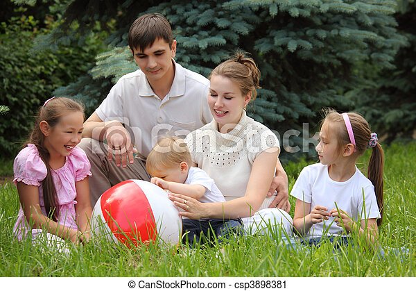 family of five outdoor in summer sit on grass with ball - csp3898381