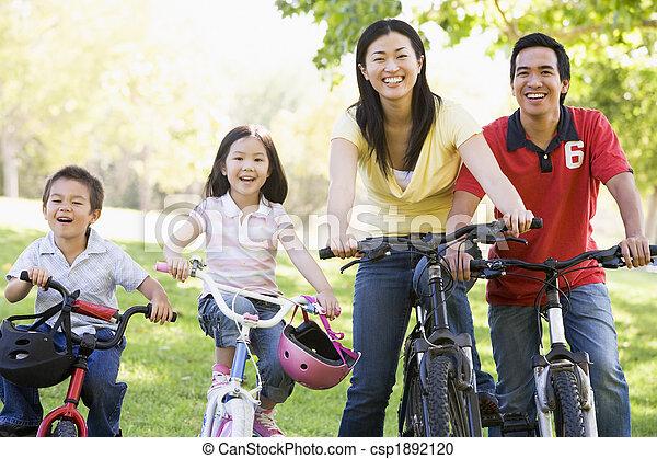 Family on bikes outdoors smiling - csp1892120