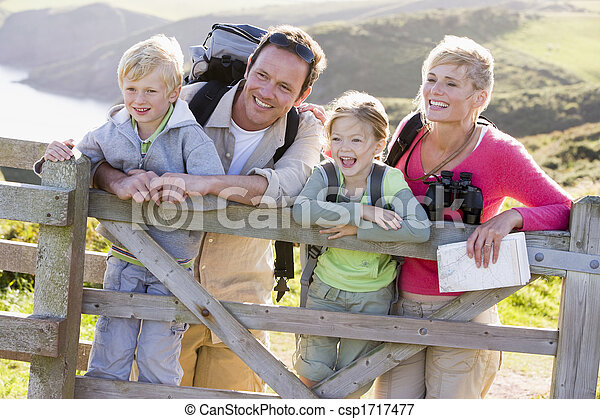 Family on cliffside path leaning on fence and smiling - csp1717477