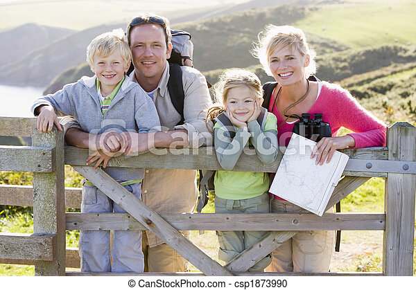 Family on cliffside path leaning on fence and smiling - csp1873990