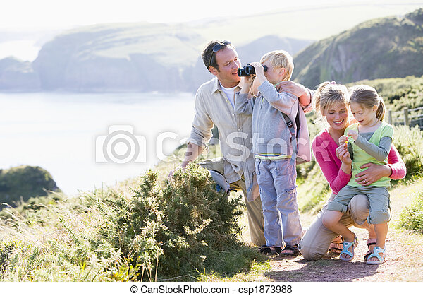 Family on cliffside path using binoculars and smiling - csp1873988