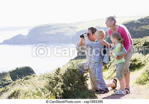 Family on cliffside path using binoculars and smiling - csp1893395