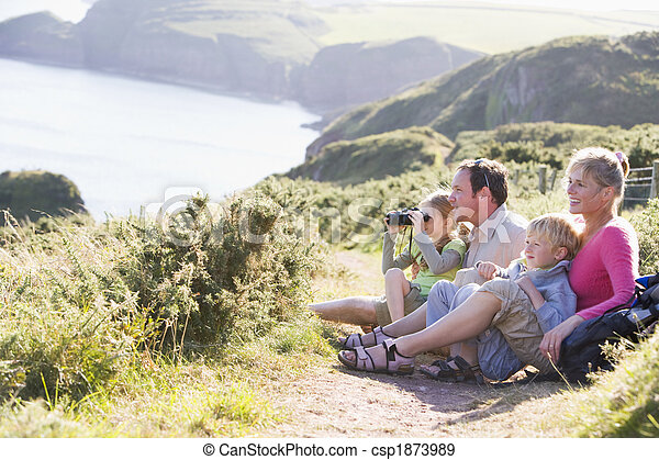 Family on cliffside path using binoculars and smiling - csp1873989