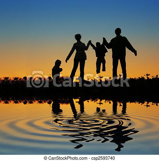 family on sunset pond - csp2593740