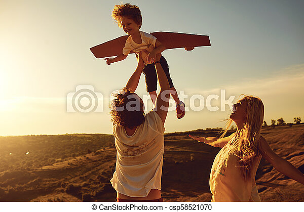 Family playing in nature at sunset - csp58521070