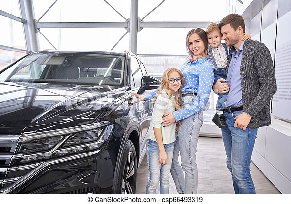 Family posing near black auto in dealership showroom. - csp66493319