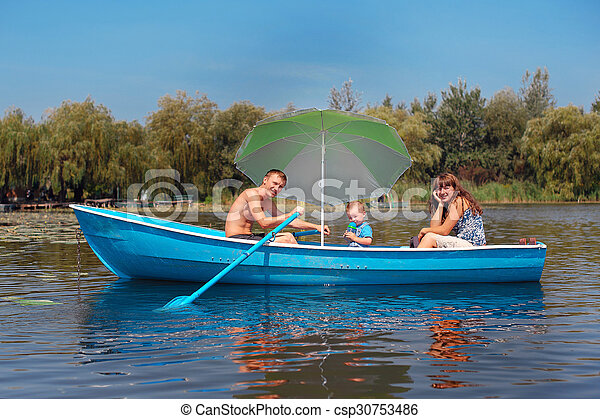 family riding on a boat in the summer - csp30753486