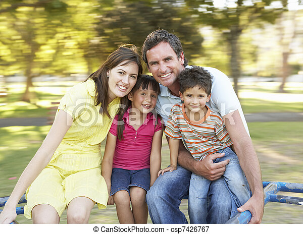 Family Riding On Roundabout In Park - csp7426767