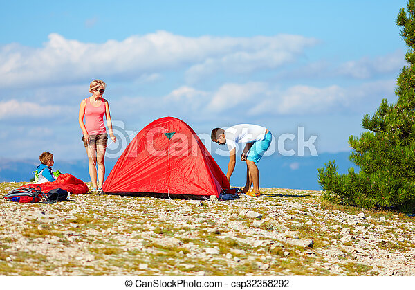 family set up a camp in mountains, active lifestyle - csp32358292