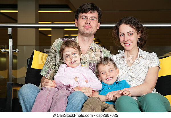 family sit on sofa in dark hall - csp2607025
