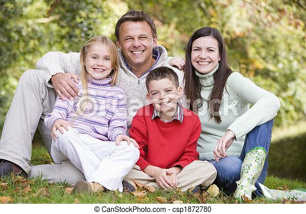 Family sitting amongst autumn trees - csp1872780