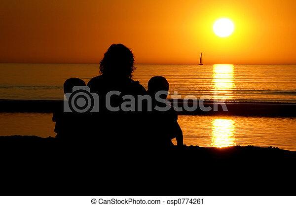 Family Sitting At Sunset - csp0774261