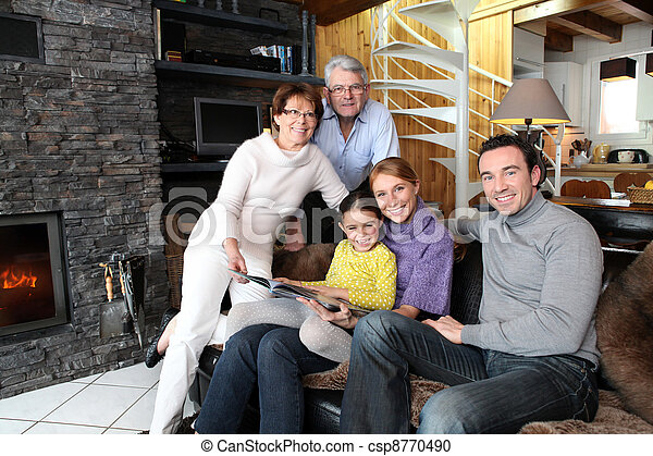Family sitting in front of a fire - csp8770490