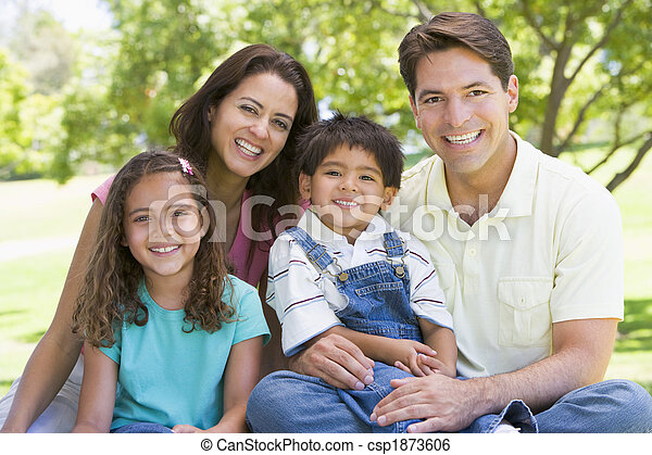 Family sitting outdoors smiling - csp1873606