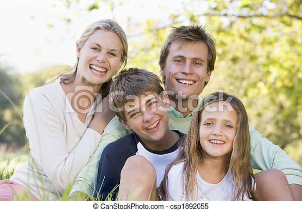 Family sitting outdoors smiling - csp1892055